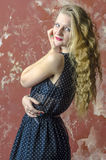 Young girl with blonde curly hair in a long dress with polka dots Stock Image