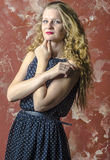 Young girl with blonde curly hair in a long dress with polka dots Royalty Free Stock Photos