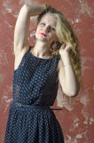 Young girl with blonde curly hair in a long dress with polka dots Stock Photos