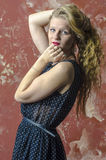Young girl with blonde curly hair in a long dress with polka dots Royalty Free Stock Photography