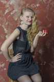 Young girl with blonde curly hair in a long dress with polka dots eat apple Royalty Free Stock Images