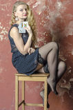 Young girl with blonde curly hair in a long dress with polka dots with playing cards Royalty Free Stock Photos