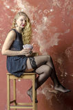 Young girl with blonde curly hair in a long dress with polka dots with playing cards Stock Photography