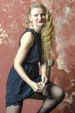 Young girl with blonde curly hair in a long dress with polka dots with playing cards Stock Image