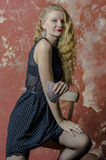 Young girl with blonde curly hair in a long dress with polka dots with playing cards Royalty Free Stock Images