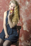 Young girl with blonde curly hair in a long dress with polka dots with teddy bear eat apple Royalty Free Stock Photo