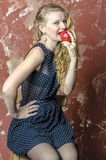 Young girl with blonde curly hair in a long dress with polka dots with teddy bear eat apple Stock Images
