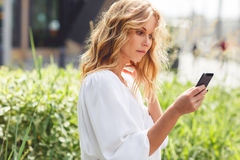 Young girl with blonde curly hair using smartphone outdoors Stock Images