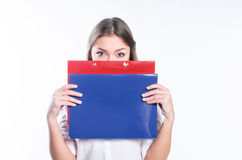 Young girl with blonde hair and green eyes is hiding her face be. Hind the office folders, isolated Stock Image