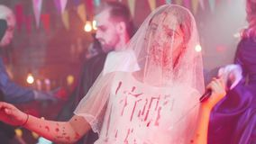 Young girl in a bloody stained bride dress with a veil on her face and a bloody knife as a halloween disguise. Halloween party stock video footage