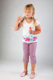 Young  girl blow out soap bubbles. Young girl blow out soap bubbles on gray background Stock Image