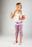 Young  girl blow out soap bubbles. Young girl blow out soap bubbles on gray background Stock Images