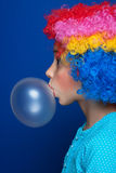 Young girl blowing bubble gum balloon. Young girl blowing chewing gum balloon over blue background stock photography