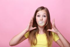 Girl blowing bubble gum. Young girl blowing bubble gum on pink background royalty free stock photo