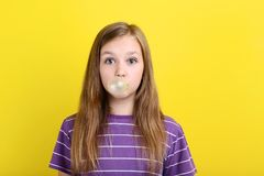 Girl blowing bubble gum. Young girl blowing bubble gum on yellow background royalty free stock photography
