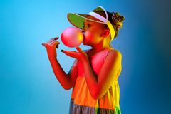 Young girl blowing bubble gum. Happy teen girl standing over trendy blue neon studio background. Beautiful female portrait. Young satisfy girl. Human emotions royalty free stock photos