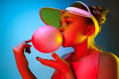 Young girl blowing bubble gum. Happy teen girl standing over trendy blue neon studio background. Beautiful female portrait. Young satisfy girl. Human emotions royalty free stock image