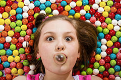 Blowing a bubble in a pile of gumballs Stock Images