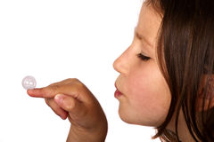 Young girl blowing a bubble off her finger Stock Photo