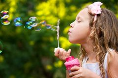 Young girl blowing bubbles. Close up portrait of cute little girl blowing bubbles in garden royalty free stock images
