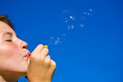 Young Girl blowing bubbles. With blue sky stock photos