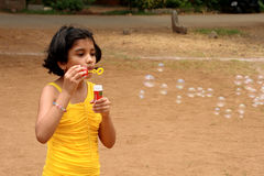 Young girl blowing bubbles Stock Photos
