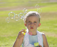 Young girl blowing bubbles stock images