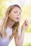 Young girl blowing bubbles outdoors Royalty Free Stock Image