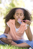 Young girl blowing bubbles outdoors stock images