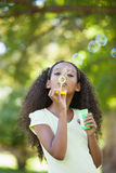Young girl blowing bubbles in the park Royalty Free Stock Image