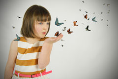 Young girl blowing butterflies Royalty Free Stock Photography
