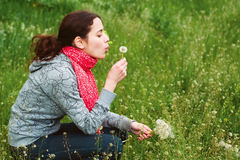 Young girl is blowing on dandelion Royalty Free Stock Image