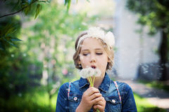 Young Girl Blowing a Dandelion Outdoor Stock Image