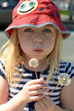 Young girl blowing dandelion. Weeds royalty free stock images
