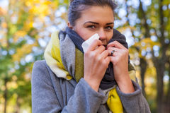 Young girl is blowing her nose. She is cold. Autumn time. Stock Image