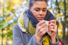 Young girl is blowing her nose. She is cold. Autumn time. Royalty Free Stock Photos