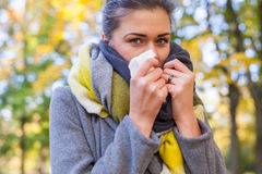 Young girl is blowing her nose. She is cold. Autumn time. Royalty Free Stock Photo