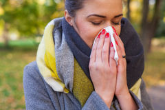Young girl is blowing her nose. She is cold. Autumn time. Stock Photo