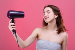 A young girl blowing herself with a stream of air from the hair dryer and enjoys closing her eyes. stock photo