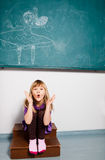 Young girl blowing kiss in classroom Royalty Free Stock Image