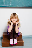Young girl blowing kiss in classroom Royalty Free Stock Photos