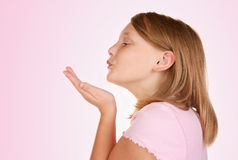 Young girl blowing a kiss on pink Royalty Free Stock Image