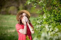 Young girl blowing nose and sneezing in tissue in front of blooming tree. Seasonal allergens affecting people. Beautiful lady has. Rhinitis royalty free stock photography