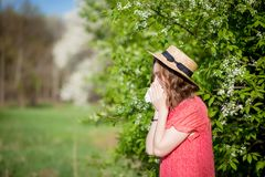 Young girl blowing nose and sneezing in tissue in front of blooming tree. Seasonal allergens affecting people. Beautiful lady has. Rhinitis stock photo