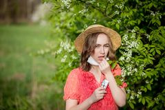 Young girl blowing nose and sneezing in tissue in front of blooming tree. Seasonal allergens affecting people. Beautiful lady has. Rhinitis royalty free stock photos