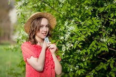 Young girl blowing nose and sneezing in tissue in front of blooming tree. Seasonal allergens affecting people. Beautiful lady has. Rhinitis stock photography