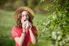 Young girl blowing nose and sneezing in tissue in front of blooming tree. Seasonal allergens affecting people. Beautiful lady has. Rhinitis stock images