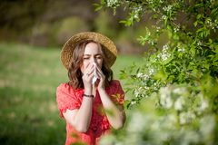 Young girl blowing nose and sneezing in tissue in front of blooming tree. Seasonal allergens affecting people. Beautiful lady has. Rhinitis royalty free stock images