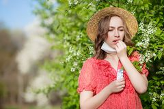 Young girl blowing nose and sneezing in tissue in front of blooming tree. Seasonal allergens affecting people. Beautiful lady has. Rhinitis stock image