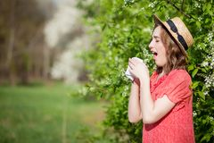 Young girl blowing nose and sneezing in tissue in front of blooming tree. Seasonal allergens affecting people. Beautiful lady has. Rhinitis royalty free stock photo